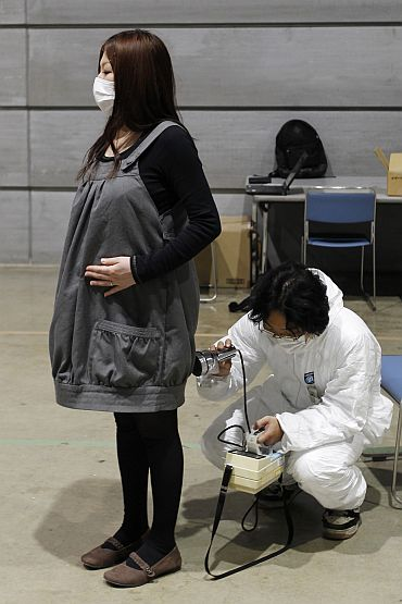 Hiromi Kobayashi, who is eight months pregnant, is tested for possible nuclear radiation exposure at an evacuation centre in Koriyama, Fukushima Prefecture
