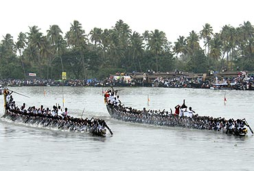 Oarsmen row their snake boats during a boat race in the waters of Punnamada Lake in Alleppy