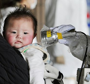 A baby undergoes a check for radiation in Fukushima City