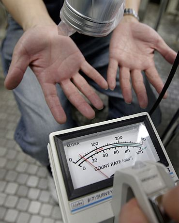 Kazumi Sato, from Soma in Fukushima, undergoes a screening test for signs of nuclear radiation by a doctor at a welfare center in Yonezawa, northern Japan