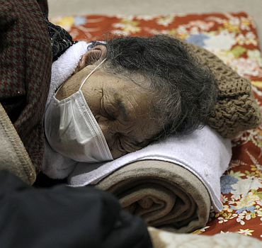 An evacuee closes her eyes at an evacuation centre set in a gymnasium in Yamagata, northern Japan