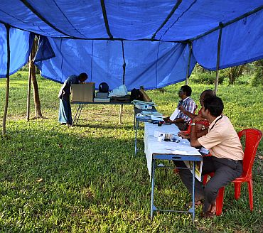 A man (Left) casts his vote at a temporary polling booth on Ramanthuruthu Island during the state assembly election