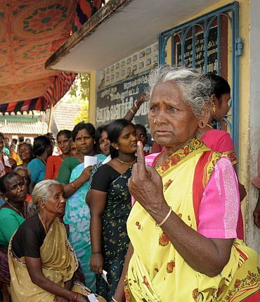 An old lady voter showing the ink mark on her finger after casting her vote at a polling booth in Katterikuppam, in Puducherry