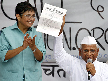 Hazare displays a note from the Indian government to his supporters as former Indian police officer and social worker Kiran Bedi watches
