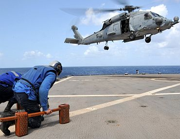 Flight crew members aboard 7th Fleet command ship USS Blue Ridge (LCC 19) prepare to chain an SH-60F Sea Hawk to the flight deck. The Sea Hawk is attached to the Black Knights of Helicopter Anti-Submarine Squadron 4 (HS-4), embarked on USS Ronald Reagan