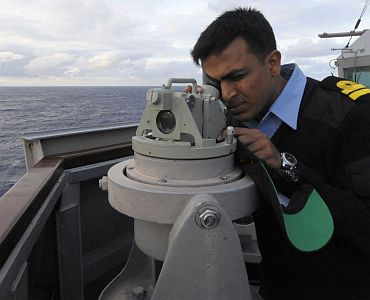 Indian Navy Liaison Officer Lt K Srinivasan looks through a gyro repeater aboard guided-missile destroyer USS Stethem (DDG 63)
