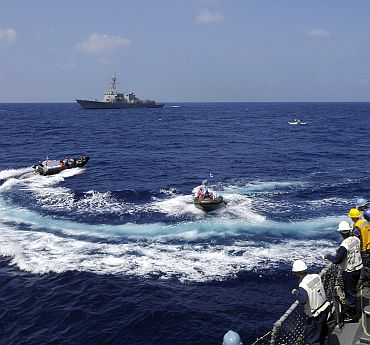 Sailors stationed aboard the guided-missile destroyer USS Stethem (DDG 63) watch Indian sailors transport officers in rigid hull inflatable boats, as part of exercise Malabar 2011