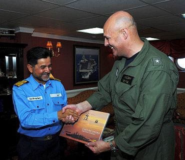 Capt Thom Burke, commanding officer of the aircraft carrier USS Ronald Reagan (CVN 76), exchanges a gift with Indian navy Rear Adm. Harish Bisht, flag officer of Commanding Eastern Fleet in the captain's in-port cabin aboard Ronald Reagan