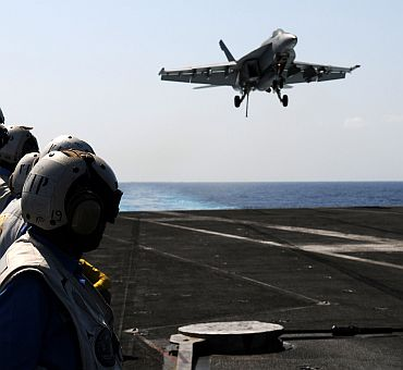 Indian naval officers observe flight operations aboard the aircraft carrier USS Ronald Reagan (CVN 76)