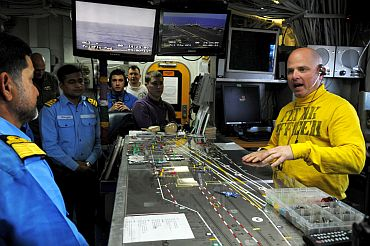 Flight Deck Officer Lt Brian Zimmerman explains how flight deck control manages the aircraft on board the aircraft carrier USS Ronald Reagan (CVN 76) to Indian naval officers