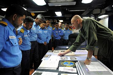 Rear Adm Robert Girrier, commander of Carrier Strike Group (CSG) 7, explains the role of the aircraft carrier USS Ronald Reagan (CVN 76) in Operation Tomodachi to Indian naval officers