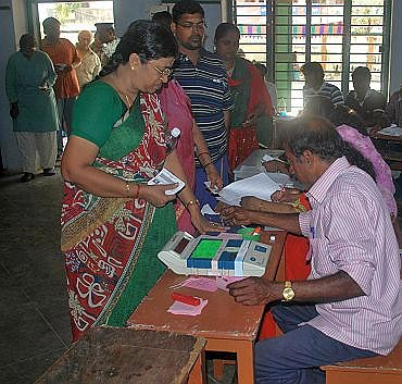 A polling officer administering indelible ink to a voter at a polling booth at Mylapore constituency