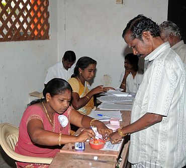 A lady poling officer administering indelible ink to the finger of a voter at a polling booth at Kanyakumari