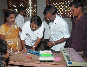 Polling officials checking the Electronic Voting Machines and other necessary inputs required for the assembly election