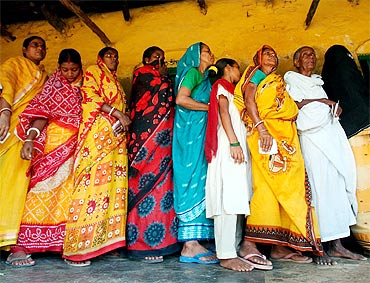 Voters stand outside a polling booth in West Bengal