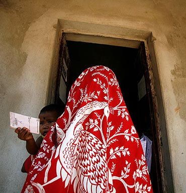 A child holds the voting card of his mother as she goes to a polling booth