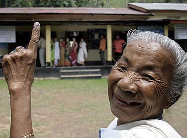 A woman shows her ink-marked finger after casting her vote at a polling station