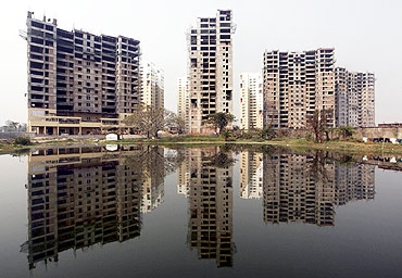 Residential apartments under construction are reflected on the surface of a pond in Kolkata