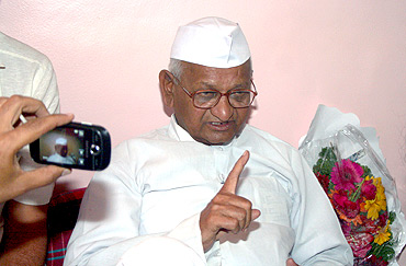 Anna Hazare speaking with reporters inside a temple in Ralegan Siddhi