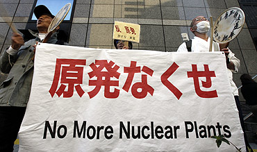 Anti-nuclear protesters and a Japanese Buddhist monk protest outside Tokyo Electric Power Co's headquarters building in Tokyo