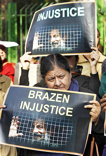Protesters hold placards during a protest against what they say is the unjust conviction of Binayak Sen, in New Delhi