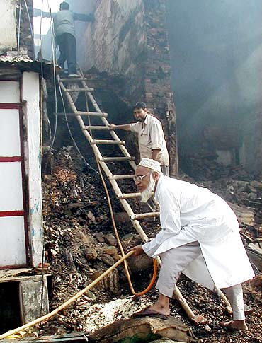 A Muslim man holds a hose outside his burning shop in a village near Ahmedabad after communal riots rocked the state in 2002