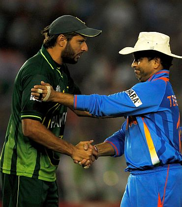 Pakistan captain Shahid Afridi congratulates cricketer Sachin Tendulkar after India beat the former's team in the World Cup semi-final match at Mohali, w