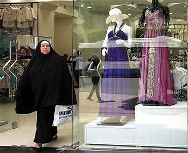 A veiled woman walks out of a shop
