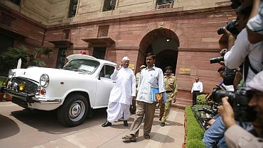 Hazare waves to photographers after attending a meeting at the finance ministry in New Delhi