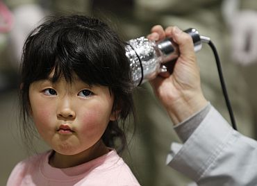 A four-year-old girl is tested for possible nuclear radiation at an evacuation centre in Koriyama, Fukushima Prefecture