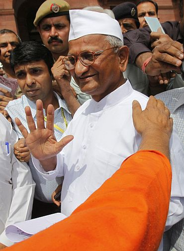 Social activist Anna Hazare gestures to photographers after attending a joint Lokpal panel meeting in New Delhi