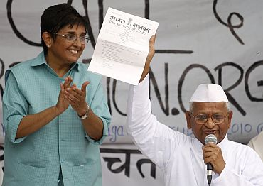Anna Hazare displays a note from the government to his supporters as Kiran Bedi watches in New Delhi