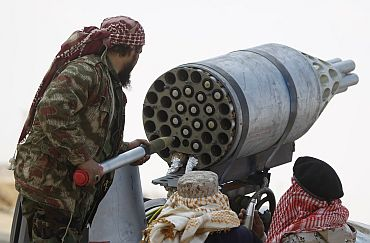 Rebel fighters man a rocket pod taken from an aircraft mounted on a pickup truck, in the front line along the western entrance of Ajdabiyah