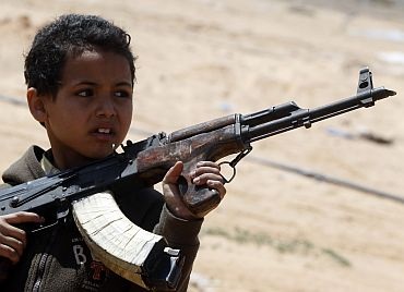 A rebel fighter's son holds a weapon near the front line along the western entrance gate of Ajdabiyah