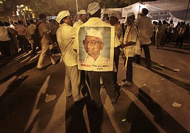 A supporter wearing a paper poster of social activist Hazare attends a protest against corruption in New Delhi