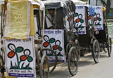 A man sits in a cycle rickshaw decorated with Trinamool Congress placards on a roadside in Kolkata