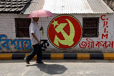 A man walks past Communist Party of India-Marxist party symbol in Kolkata
