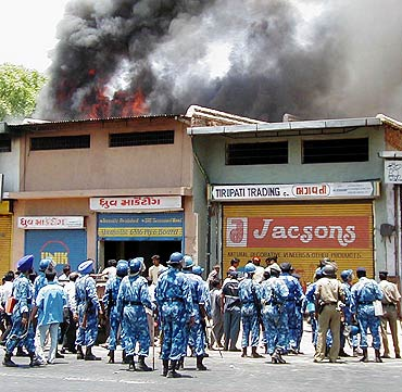 Riot police watch as smoke rises from shops in Ahmedabad during the 2002 riots