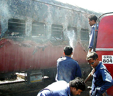 Firemen try to put out a fire on the Sabarmati Express on February 27, 2002