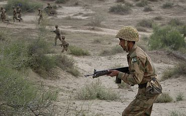 Pakistan Army infantry troops charge through the Khudai Range while taking part in military exercises