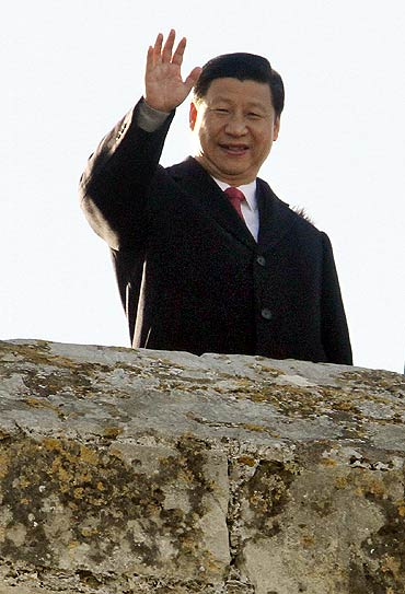 China's Vice President Xi Jinping waves to photographers as he visits the Bellver Castle in Spain