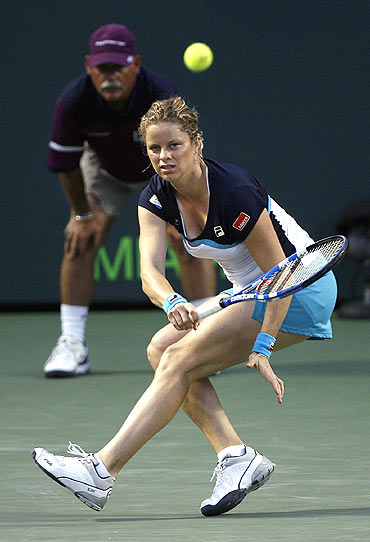 Kim Clijsters of Belgium returns a shot to Victoria Azarenka of Belarus in Florida