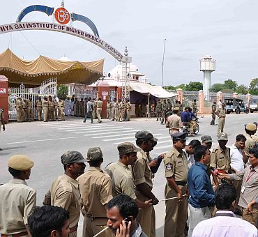 Devotees and mediapersons gather in front of the hospital in Puttaparthi where Sathya Sai Baba passed away on Sunday morning