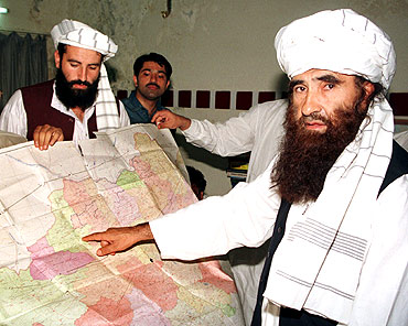 Jalaluddin Haqqani (Right) points to a map of Afghanistan during a visit to Islamabad in Oct 2001