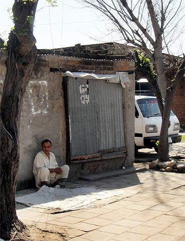 A man sits by a shop at a camp for Kashmiri migrants in Jammu
