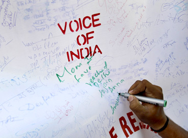 A supporter of social activist Anna Hazare writes on a canvas during a campaign against corruption