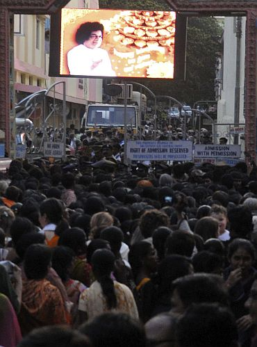 Devotees wait to enter the ashram to pay their last respects to Sathya Sai Baba