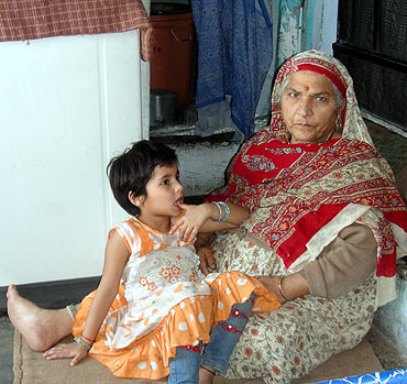 Ravi Below's mother and her grandchild. Three generation share their small camp home.