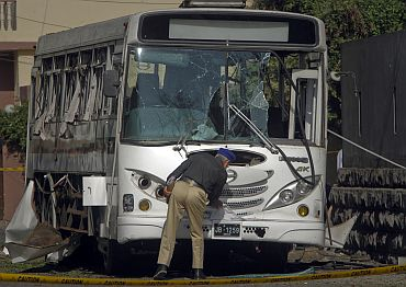 A security official examines a bus carrying Pakistani navy officials after it was damaged by a bo