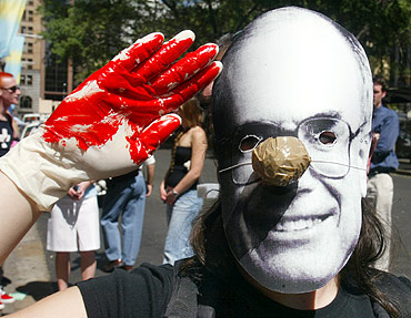 A protester salutes with fake blood on her hands as she wears a mask of Australian Prime Minister John Howard in Sydney